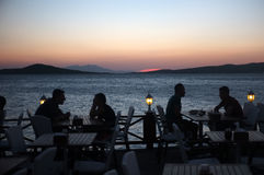 People sit in seaside restaurant at dusk Royalty Free Stock Photography