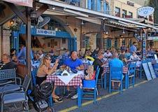 People sit in sidewalk street cafe in Chania waterfront, Crete, stock image
