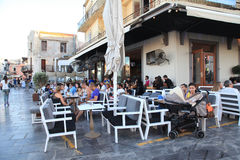 People sit in sidewalk street cafe in Rethymno waterfront, Crete royalty free stock photography
