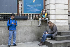 People sit on the steps, waiting for friends Stock Photo