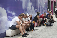People sit on the street near the pub, drinking beer and smoking Stock Photo