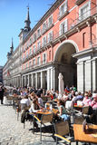 People sit at tables in cafe at Plaza Mayor Royalty Free Stock Image