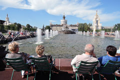 People sit by water. Architecture of VDNKH park in Moscow. Royalty Free Stock Photo