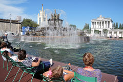 People sit by water. Architecture of VDNKH park in Moscow. Royalty Free Stock Photography