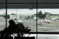 People sitting in the airport lounge waiting for boarding on a f. Light, seen through a window airfield with planes arrived Stock Photo