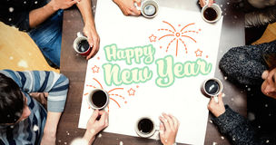 People sitting around table drinking coffee against new year graphic Stock Photo