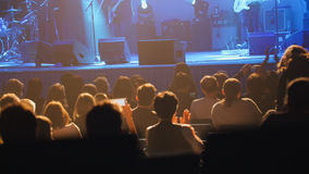 People sitting in auditorium at rock concert - Abstract blurred royalty free stock photo