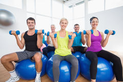 People sitting on balls and lifting weights in fitness club Royalty Free Stock Images