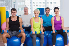 People sitting on balls and lifting weights in gym class Stock Photo