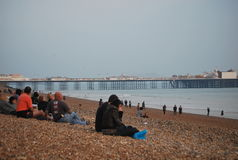 People sitting on the beach in Brighton, the UK Royalty Free Stock Image