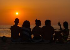 People sitting on a beach looking at  sunset Stock Image