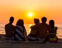 People sitting on a beach looking at  sunset. Silhouettes a young people sitting on a beach looking at  sunset Royalty Free Stock Photography