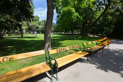 People sitting on bench, grass at Stadtpark, City Park in Vienna, Austria during summer season stock photography