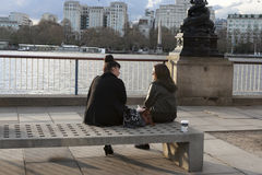 People Sitting on  Bench on London `s South Bank Overlooking Riv Stock Image