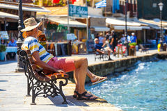 People sitting on the bench in the old harbor of Chania on Crete, Greece Stock Photo