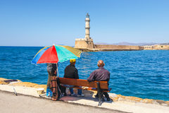 People sitting on the bench in the old harbor of Chania on Crete, Greece Stock Image