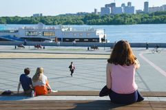 People are sitting on a bench on the waterfront. royalty free stock photos