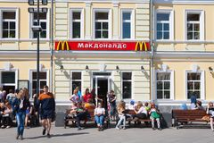 People sitting on benches near McDonald's restaurant building Royalty Free Stock Images