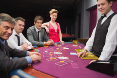 People sitting at blackjack table and smiling Stock Image