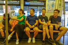 People sitting on BTS train in Bangkok, Thailand stock images