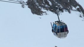 People sitting in cable car, moving up towards skiing run in snowy mountains. Stock footage stock footage
