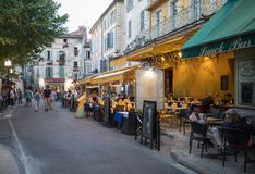 People sitting at a cafe in Place du Forum, Arles, Provence, France. Arles, France - June 24, 2017: People sitting at a cafe in Place du Forum, Arles, Provence Stock Image