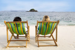 People sitting on chairs at the beach Royalty Free Stock Photo