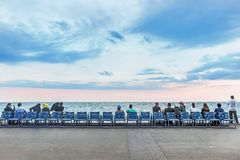 People sitting on chairs at coast in nice Royalty Free Stock Image