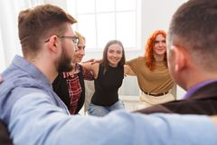 People sitting in circle, hugging each other. Happy people sitting in circle, hugging each other. Meeting of support group, copy space. Teambuilding concept stock photos