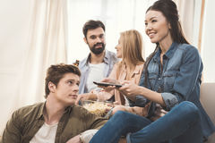 People sitting on couch with popcorn and beer Royalty Free Stock Photography