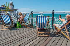 People sitting in deck chair s on the pier. BRIGHTON, UK - JULY 28: Holiday makers enjoy the sun on Brightons world famouse pier in July 2013 Stock Images