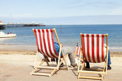 People sitting in deckchairs at Llandudno seaside holiday resort. Looking out to sea. Image taken from behind Royalty Free Stock Photo