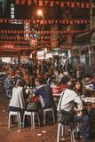 People sitting and eating street food at the evening Temple Street Market in Hong Kong stock images