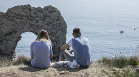 People sitting at the edge of a cliffs, Durdle Door. The picture shows some people sitting at the edge of a cliff and blue waters of the sea in Durdle Door Stock Image
