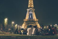 People sitting by the Eiffel Tower at night Royalty Free Stock Image