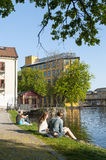 People sitting on the embankment to Motala stream Stock Image