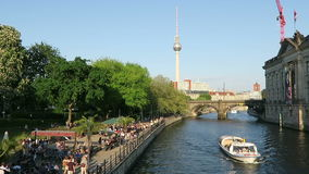 People sitting in the evening sun at Spree river cafe in Berlin. In background tv tower of Alexanderplatz. Tourist boat comes alon stock footage