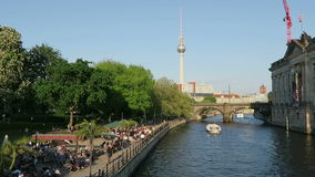 People sitting in the evening sun at Spree river cafe in Berlin. In background tv tower of Alexanderplatz. Tourist boat comes alon. BERLIN, BERLIN/ GERMANY MAY stock footage