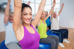 People sitting on exercise balls in fitness class Royalty Free Stock Photo