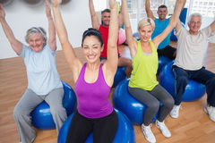 People sitting on exercise balls with hands raised Stock Photo