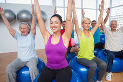People sitting on exercise balls with hands raised Royalty Free Stock Image