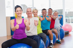 People sitting on exercising balls gesturing thumbs up Royalty Free Stock Photos