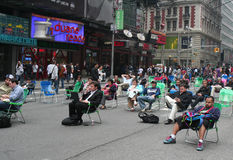 People sitting on folding chairs in Times Square. Two days after making the busy Times Square intersection people are relaxing on folding chairs royalty free stock images