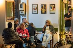 People sitting having a drink at O Platanos, a traditional coffee shop in Pylos, Greece stock photography