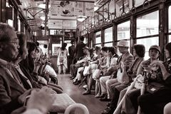 People sitting in a historical street car train in Kyoto stock images