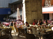 People sitting at an Italian outdoor cafe Stock Images