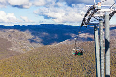 People sitting on Kosciuszko Express Chairlift in front of beaut Stock Photography