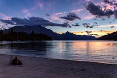 People sitting by the lake Wakatipu and watching beautiful sunset in Queenstown royalty free stock photo