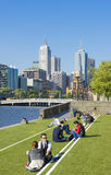 People sitting on lawn in Southbank and Melbourne skyline Royalty Free Stock Images