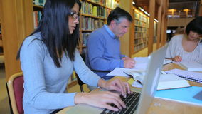 People sitting at the library and doing their assignments. With woman using laptop in college stock footage